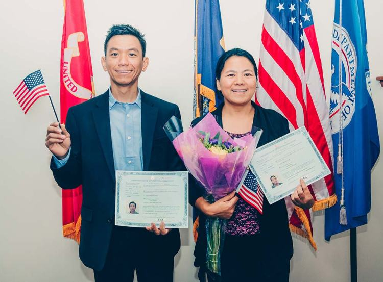 Photo of smiling man and woman holding U.S. flags and certificates of U.S. citizenship.