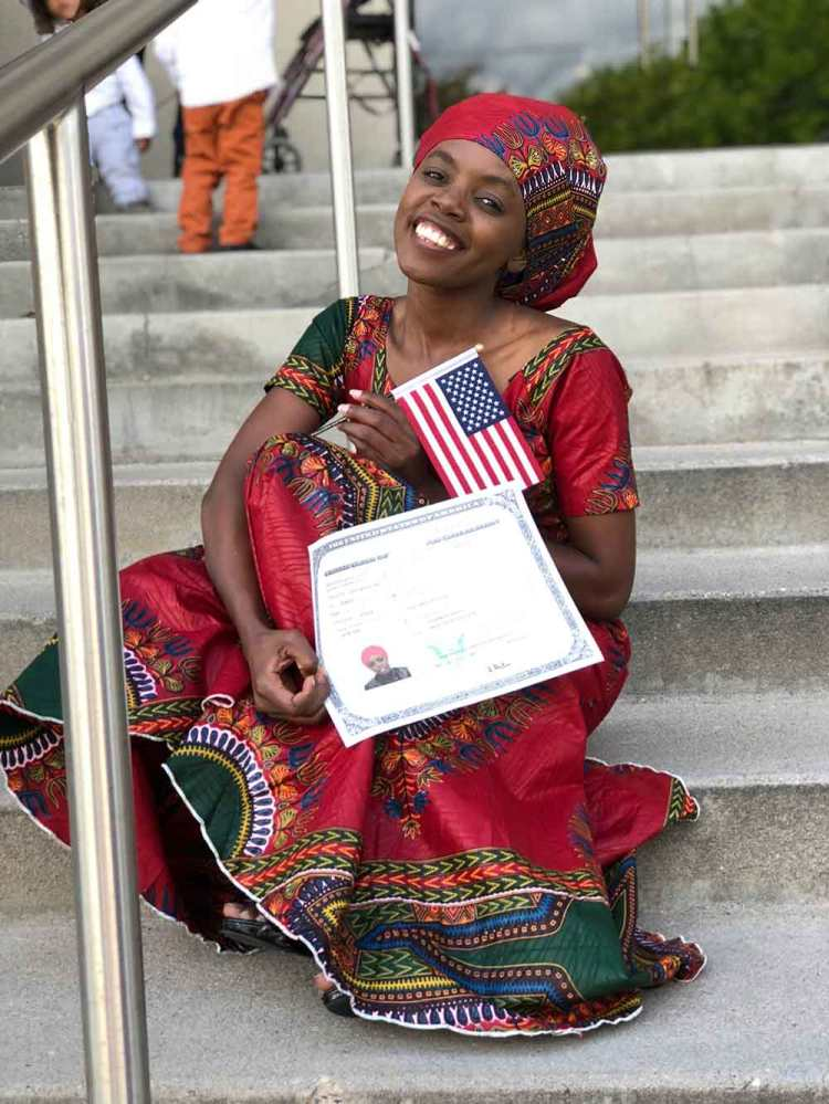 Photo of smiling woman holding U.S. flag and certificate of U.S. citizenship .